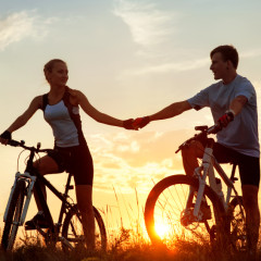 Silhouette of young couple on sporty bicycles against sunset