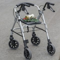 Rollator walker with grave candle, symbol of grief and transience.